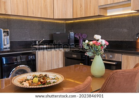 Kitchen area in luxury apartment show home showing open plan interior design decor furnishing with dining table Royalty-Free Stock Photo #2023846901