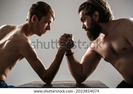 Heavily muscled bearded man arm wrestling a puny weak man. Arms wrestling thin hand, big strong arm in studio. Two man's hands clasped arm wrestling, strong and weak, unequal match. Arm wrestling.