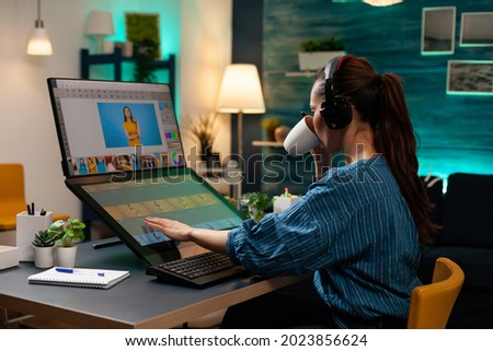 Woman with editor occupation wearing headphones at studio office desk. Professional graphic artist working on picture editing background for template using touchpad monitor screen