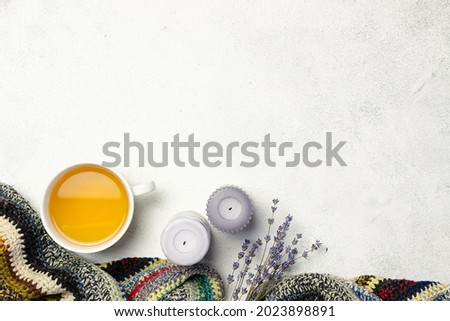Cozy Hygge style composition with handmade woolen plaid, herbal tea, candles and dry lavender bouquet on white marble background, copy space for your design. Royalty-Free Stock Photo #2023898891