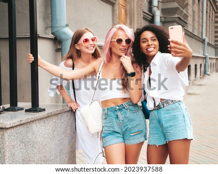 Three young beautiful smiling hipster female in trendy summer clothes.Sexy carefree multiracial women posing on the street background.Positive models having fun in sunglasses. Taking selfie photos