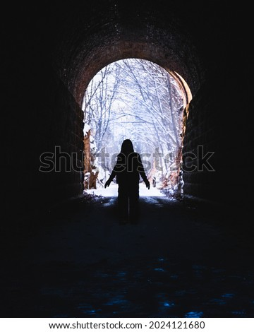Silhouette of woman standing in former railroad tunnel converted into recreational area in winter; snow covered trees in background