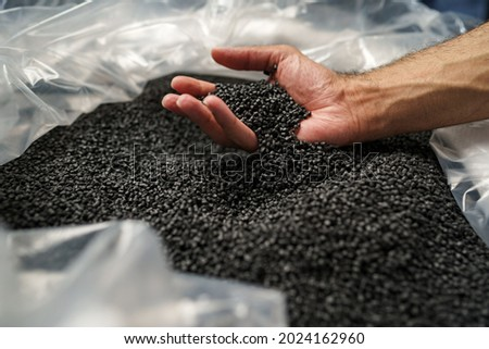 Close up of male hand holding plastic polymer granules Royalty-Free Stock Photo #2024162960