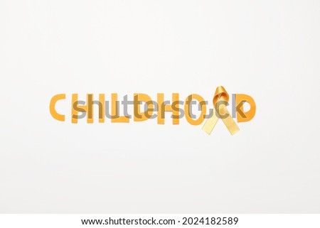 Golden ribbon and word CHILDHOOD on white background. Cancer awareness concept Royalty-Free Stock Photo #2024182589