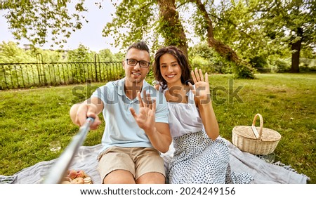 leisure and people concept - happy couple having picnic and taking picture with selfie stick at summer park