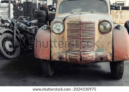 Many rusty abandoned forgotten antique oldtimer old car and motorcycles at junkyard factory storage warehouse indoors. Classic vintage retro vehicles detail garage workshop restore renovation station Royalty-Free Stock Photo #2024330975