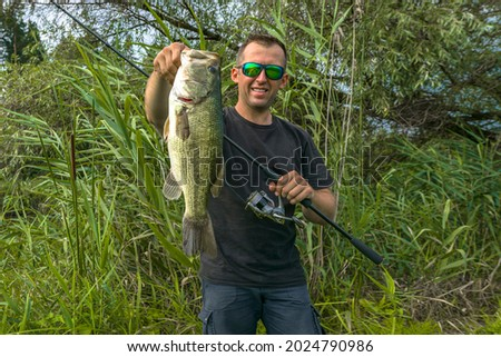 Bass fishing. Big bass fish in hands of pleased fisherman with spinning rod. Largemouth perch at pond Royalty-Free Stock Photo #2024790986