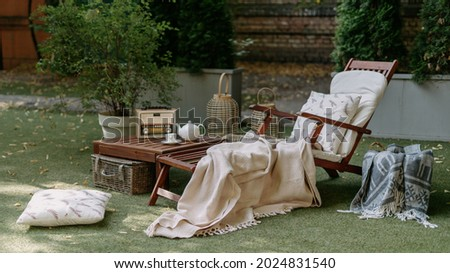 Outdoor garden wooden furniture at autumn nature, green grass. Nobody at home backyard with chair, lounge. Relax at outside terrace with blankets, pillows at retro, vintage decoration. Royalty-Free Stock Photo #2024831540