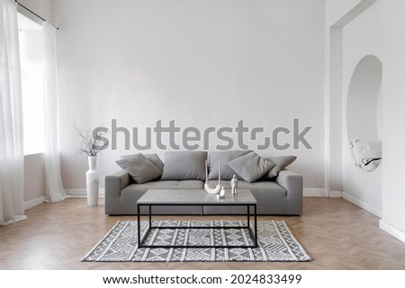Room interior, modern home design with furniture. Grey sofa at white apartment, living room in simple style. Scandinavian flat with stylish minimal decor, space for relax. Royalty-Free Stock Photo #2024833499