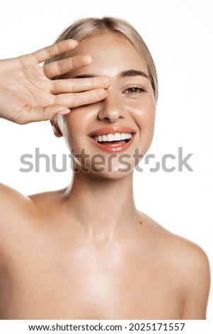 Natural beauty. Feminine blond girl laughing with white, perfect smile, looking happy, touching hydrated, glowing facial skin, head and shoulders portrait, studio background Royalty-Free Stock Photo #2025171557