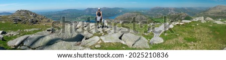 Female Hiker drinking water and looking onto dramatic Fjord landscape in Southern Norway