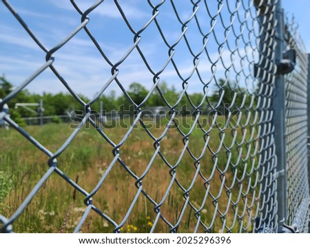 A closeup of a fence that is protecting a property. The metal gate is a chain link fence with barbed wire at the very top of it. Royalty-Free Stock Photo #2025296396