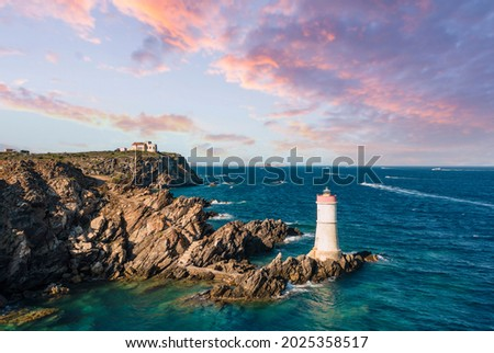 View from above, stunning aerial view of an old and beautiful lighthouse located on a rocky coast bathed by a rough sea. Faro di Capo Ferro, Porto Cervo, Sardinia, Italy. Royalty-Free Stock Photo #2025358517