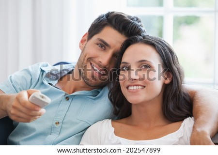 Attractive couple watching tv on the couch at home in living room #202547899
