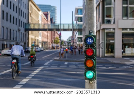 Selective focus, Green traffic light with bicycle symbol on sidewalk beside bicycle lane in Europe and defocus of people ride bicycle. Royalty-Free Stock Photo #2025571310
