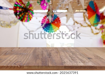 Jewish festival of Sukkot. Traditional succah (hut) with decorations. Empty wooden old table for product display and presentation. Royalty-Free Stock Photo #2025637391