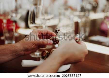 Cropped picture of man eating escargots with special fork, white ceramic pan with cooked snails, sitting at restaurant and enjoying delicious meal with wine, selective focus on hands. Sea food concept