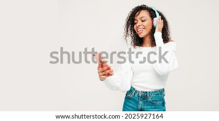 Beautiful black woman with afro curls hairstyle.Smiling model in sweater and jeans.Sexy carefree female listening music in wireless headphones.Posing in studio on white background.Holding smartphone