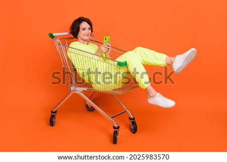 Portrait of attractive cheery funny focused girl sitting in shopping cart chatting blogging isolated over bright orange color background Royalty-Free Stock Photo #2025983570