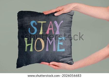 Soft fabric pillow holding by hand with stay home text Royalty-Free Stock Photo #2026056683