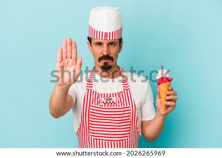 Young caucasian ice cream maker holding a ice cream isolated on blue background standing with outstretched hand showing stop sign, preventing you.