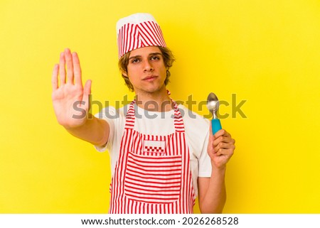 Young ice cream maker man with makeup holding spoon isolated on yellow background  standing with outstretched hand showing stop sign, preventing you.