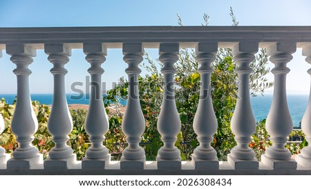 Traditional Greek architecture white balcony balusters. View on clear blue Aegean sea coast. Summer scenic view from country house terrace near Athens, Greece Royalty-Free Stock Photo #2026308434