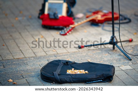 Street performers busking money. Street musician, guitar player make money. Guitar bag with coins and equipment of street musician in background.  Royalty-Free Stock Photo #2026343942