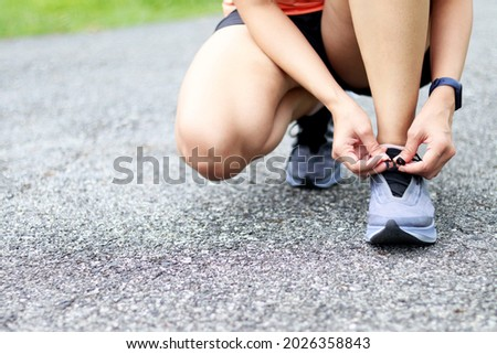 woman tying shoe laces. A female runner is lacing her shoes to prepare for her run. Royalty-Free Stock Photo #2026358843