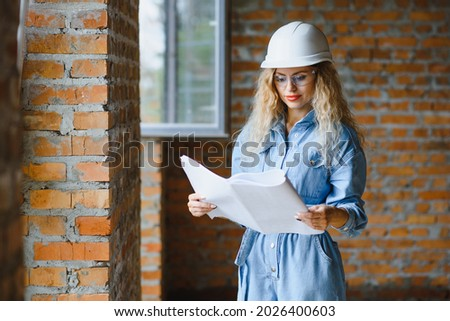 Construction concept. Pretty female builder in overalls and helmet working on construction site.