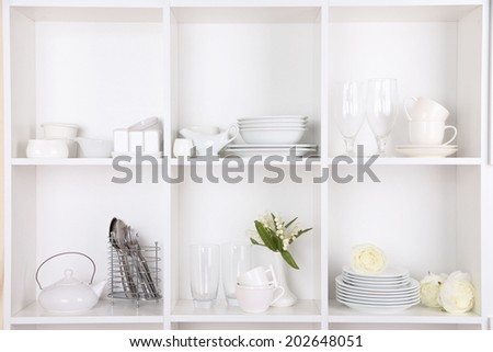 Different white clean dishes on wooden shelves #202648051