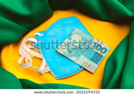 Real - BRL A bill of one hundred reais on a n95 blue mask and a representation of the Brazilian flag in the composition. Concept of the Brazilian economy during the new coronavirus pandemic.  Royalty-Free Stock Photo #2026594550