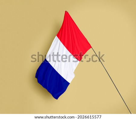 France flag fluttering on a subtle yellow background Royalty-Free Stock Photo #2026615577