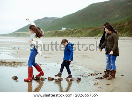 Kids walking on stones at the beach