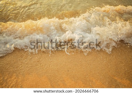 Scenic seascape. Splashing waves at sandy beach. Sunset time. Waterscape for background. Selected soft art focus. Sunlight reflection on the water and wet sand. Balangan beach, Bali, Indonesia Royalty-Free Stock Photo #2026666706
