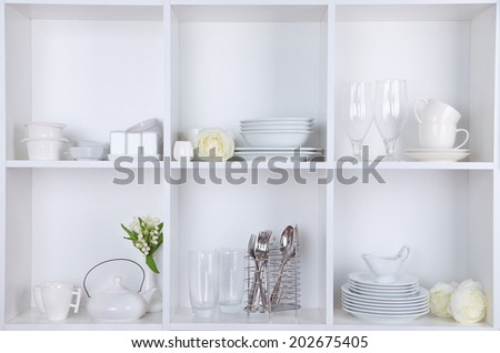 Different white clean dishes on wooden shelves #202675405