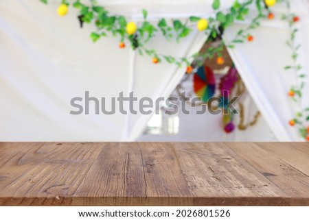 Jewish festival of Sukkot. Traditional succah (hut) with decorations. Empty wooden old table for product display and presentation. Royalty-Free Stock Photo #2026801526