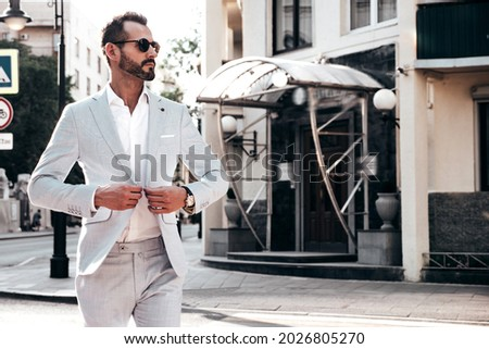 Portrait of handsome confident stylish hipster lambersexual model.Sexy modern man dressed in elegant white suit. Fashion male posing in the street background in Europe city at sunset. In sunglasses Royalty-Free Stock Photo #2026805270