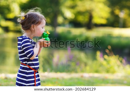 Adorable little girl giving a kiss to rubber frog. Outdoors. Fairytale concept
