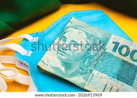 Real - BRL A bill of one hundred reais on a n95 blue mask and a representation of the Brazilian flag in the composition. Concept of the Brazilian economy during the new coronavirus pandemic.  Royalty-Free Stock Photo #2026913969