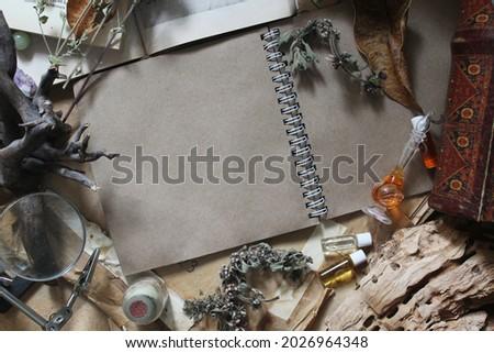 A craft paper album lies among mystical accessories.
