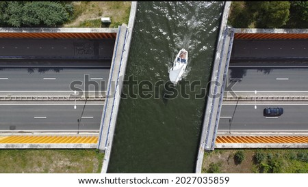 Aerial view of modern aqueduct or water bridge is constructed to convey watercourses across gaps showing a sailboat moving over the infrastructure and vehicles cars driving under Royalty-Free Stock Photo #2027035859