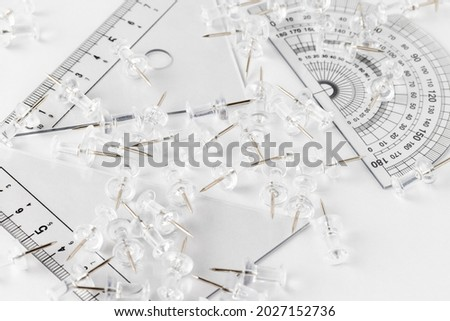 Set square ,protractor and scattered thumbtacks on a white table