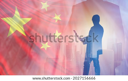 Businessman with laptop on background of flag of China. Business in China. Silhouette of Chinese businessman. Entrepreneurship with People Republic of China. Business partnership concept with Chinese Royalty-Free Stock Photo #2027156666