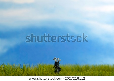A golf cart bag grass stand at meadow field with bright cloud sky background. Image photo