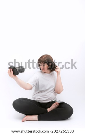 Young woman in sportswear takes selfie with professional camera. Girl sits in lotus position and takes pictures of herself