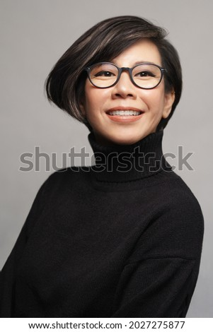 Beautiful studio portrait of a stylish 40s asian executive woman with eye glasses in black turtleneck top smiling with confident and satisfy. Model, Eyewear, Perfect Ageing Skin, Teeth, ShortHairstyle Royalty-Free Stock Photo #2027275877