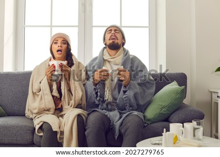 Funny young couple in warm hats, wrapped in blankets, sitting together on couch at home and sneezing in paper tissues. Sick husband and wife suffering from unpleasant symptoms of bad cold or flu virus Royalty-Free Stock Photo #2027279765