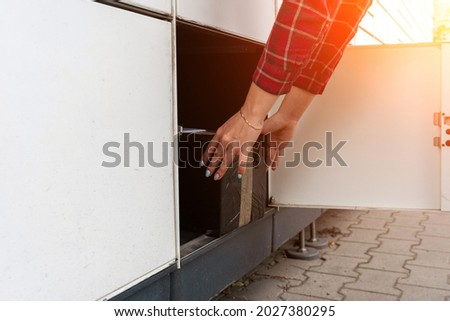 Post locker. Delivery automat terminal and hands with parcel courier box. Parcel delivery, pickup point with lockers, hand with parcel, contactless pack delivery Royalty-Free Stock Photo #2027380295