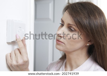 Woman Adjusting Thermostat On Central Heating Control #202741939